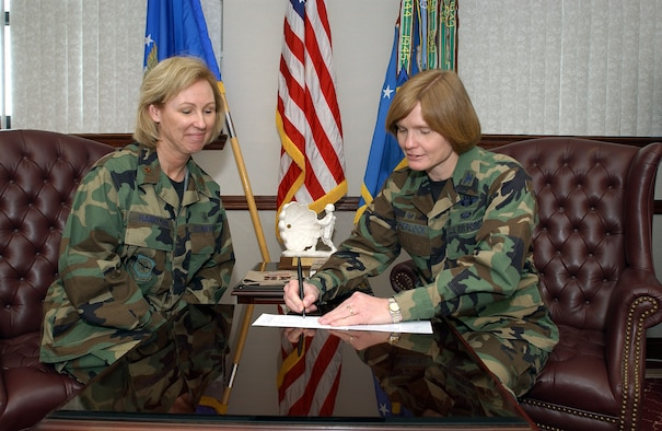 Maj. Kenny Harryman, Air Force Assistance Fund project officer here, looks on while Col. Lyn Sherlock, 60th Air Mobility Wing commander, signs her pledge for this year's AFAF campaign. The campaign kicked off March 24 and runs through May 4. (U.S. Air Force photo by Andre Mansour)