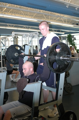 Senior Airman Bradley Parncutt, 60th Communications Squadron, provides a spot for Staff Sgt. Jeffrey Mitchell, 60th CS. Patrons are encouraged to provide a spot to others in the weightroom. (U.S. Air Force photo by Staff Sgt. Raymond Hoy)