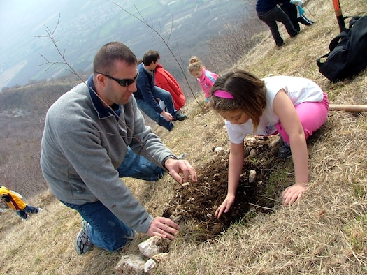 Tech. Sgt. Roy Hensley, 31st Logistics Readiness Squadron vehicle operations supervisor, and his daughter Kaylee, age 10, plant a tree in Giais Saturday. About 200 local and base residents came out to participate in the 21-year-old tree planting tradition.
