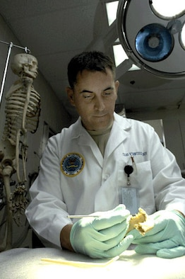 HICKAM AIR FORCE BASE, Hawaii -- Odontologist Lt. Col. Gregory Silver, of the Joint POW/MIA Accounting Command's Central Identification Laboratory, examines a partially edentulous mandible. (JPAC photo by U.S. Navy Photographer's Mate 2nd Class Elizabeth A. Edwards)