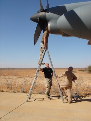Master Sgt. Steven Ashley, 746th Expeditionary Airlift Squadron, examines an engine that broke on a C-130 Hercules mission to the Horn of Africa. Senior Airman Christopher Sutton (black shirt), 746th Aircraft Maintenance Unit crew chief, and Senior Master Sgt. David Bright, 746th EAS flight engineer, watch from below. (U.S. Air Force photo/Maj. Ann Peru Knabe)
