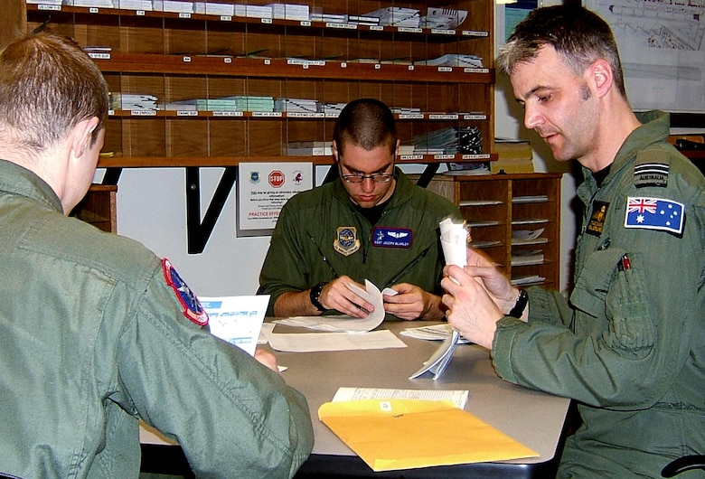 """Flight Lieutenant Craig Chaseling, Royal Australian Air Force exchange pilot, debriefs his crew after returning from a refueling trip from Alaska. """"He is always in the squadron working really hard trying to get everybody up-to-date on their training requirements,"""" said 1st Lieutenant Jocelyn Smith, the mission's co-pilot. """"He is very efficient at his job, and it's obvious why he has been selected as the instructor pilot of the quarter."""" (U.S. Air Force photo by Shadi May.)"""