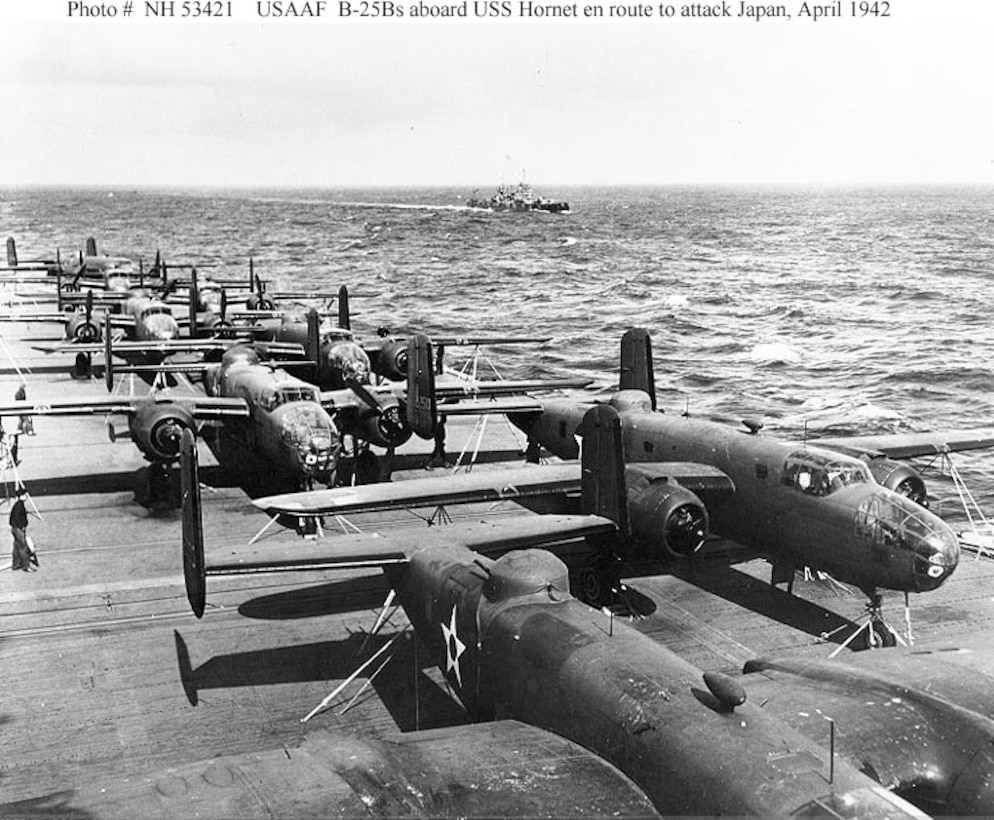 View from the island of USS Hornet (CV-8), while en route to the mission's launching point. USS Nashville (CL-43) is in the distance. Eight of the mission's 16 B-25B bombers are visible on the carrier's flight deck. Aircraft at right is tail No. 40-2250 and mission plane No. 10. 2nd Lt. Richard O. Joyce piloted the aircraft to targets in the Tokyo area. (U.S. Navy photo)