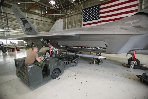EDWARDS AIR FORCE BASE, Calif. - Senior Airman Daniel Myers, Staff Sgt. Daphne Jaehn and Staff Sgt. John Davenport load an AIM-120D Advanced Medium Range Air-to-Air Missile on an F-22A Raptor recently in preparation for noise and vibration testing here. The Airmen are all part of the 412th Aircraft Maintenance Squadron and are assigned to the F-22 Combined Test Force weapons flight. (Air Force photo by Kevin Robertson)
