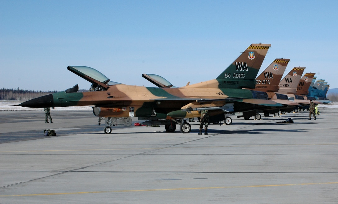 F-16 Fighting Falcons from the 64th Aggressor Squadron at Nellis Air Force Base, Nev., line the flightline at Eielson AFB, Alaska, on Tuesday, April 18, 2006, for Red Flag - Alaska.  The exercise, formerly known as Cope Thunder, provides joint offensive counter-air, interdiction, close-air support and large-force employment training in a simulated combat environment. Red Flag - Alaska runs through May 5. (U.S. Air Force photo/Airman 1st Class Justin Weaver)