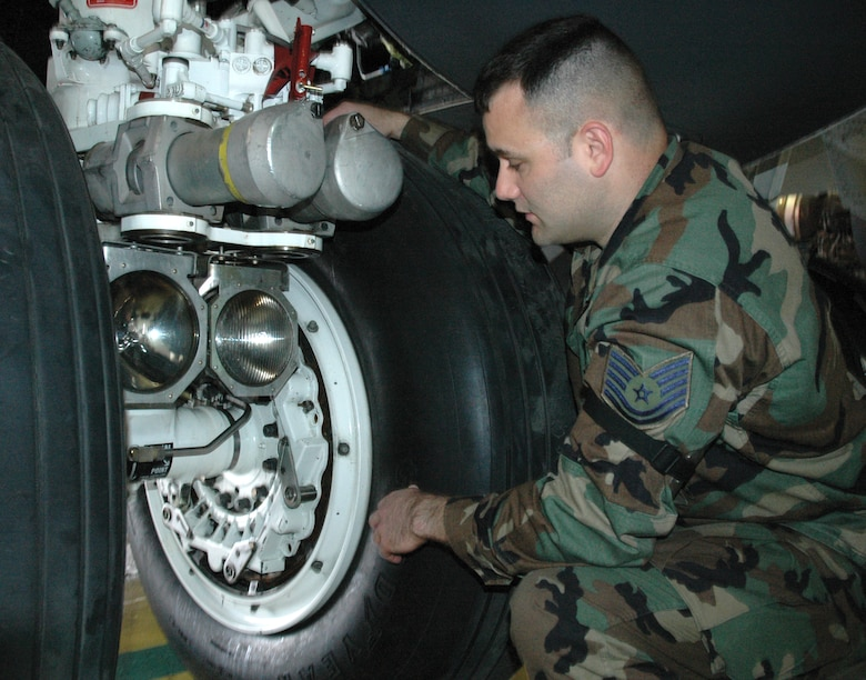 Tech Sgt. James Mazurek, 5th Maintenance Squadron, shows where a tow bar hooking up to the main landing gear of a B-52H Stratofortress can cause damage. (U.S. Air Force photo by Senior Airman Danny Monahan)