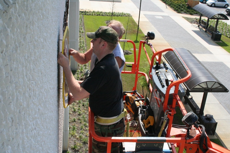 Staff Sgt. Peter Laing and Richard Lawson, 16th Civil Engineer Squadron, mount the Air Force Special Operations Command and 16th Special Operations Wing emblems on building 90210 Wednesday. The emblems were removed from the building for about two weeks to be refurbished and repainted.