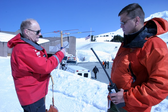 """Mr. Hal Lillywhite, Portland Mountain Rescue volunteer and author of """"Bring yourself back alive"""" (left) and Capt. Chris Bernard, 304th Rescue Squadron combat rescue office use the Yaggi directional antenna to track the transmitting beacon from a Portland Mountain Locator Unit worn by the missing climbers in a search and rescue mock exercise scenario on Mount Hood, Ore. April 22, 2006. (U.S. Air Force Photo/Ruby Zarzyczny)"""