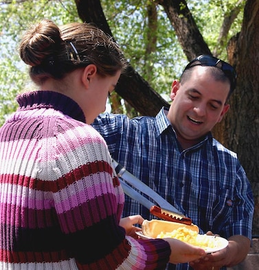 CANNON AIR FORCE BASE, N.M. - Tech. Sgt. Miguel Cruz, 27th Fighter Wing legal office, dishes out a hot dog to Madison Bridges, daughter of Chaplain (Capt.) Donald Bridges during a wing staff agency picnic at Unity Park April 21. About 75 Airmen and their families attended the outing. (U.S. Air Force photo by Janet Taylor-Birkey)