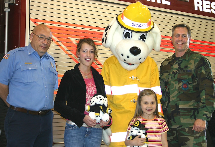 CANNON AIR FORCE BASE, N.M. - Emily Aulson of Clovis and Michaela Williams, 5, daughter of Tech. Sgt. and Mrs. Nick Williams won  miniature fire dogs from the Cannon Fire Department. Emily and Michaela found 15 fire and safety hazards in the fire safety house at the Kite Karnival, April 8. The names of everyone who found the 15 items were placed in a hat and two winners were drawn. Presenting the awards are Mr. Tony Bogusz, Sparky and Chief Master Sgt. Ivan Godwin of the Cannon Fire Department. (U.S. Air Force photo by Janet Taylor-Birkey)