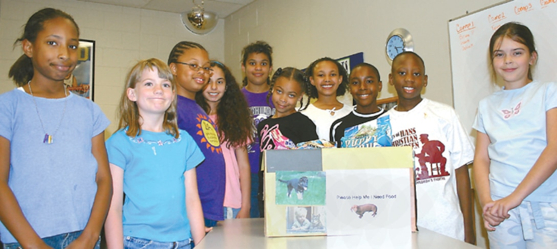 "CANNON AIR FORCE BASE, N.M. - Members of Cannon's Torch Club gather around a box of animal food they donated to the Clovis Animal Shelter April 19. The club is for ""tween""agers, from nine to 12 years old at the Cannon youth center. The club started in February and meets at 4 p.m. on Wednesdays. It reinforces service to the community and provides education and fitness guidelines in a social atmosphere. For more information, contact Thomasine Darnes at 784-2747. (U.S. Air Force photo by Janet Taylor-Birkey)"