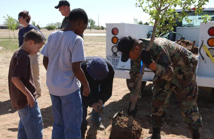 CANNON AIR FORCE BASE, N.M. - Staff Sgt. Jose Guardiola, 27th  Civil Engineer Squadron, plants a tree at Doc Stewart Park April 19 as part of Earth Day activities conducted by Cannon Airmen and students from Ranchvale Elementary. (U.S. Air Force photo by Staff Sgt. April Wickes)