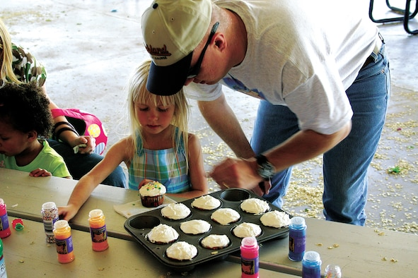 CANNON AIR FORCE BASE, N.M. - Tech. Sgt. Rodney Arnold, 27th Aeromedical Dental Squadron, helps his daughter Rachael, age 4, decorate her own cupcake under the pavilion at Unity Park. Children were invited to decorate cupcakes as well as decorating egg-shaped marshmallows. (U.S. Air Force photo by Staff Sgt. Craig Seals)