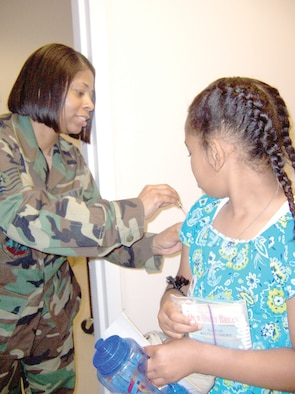 """Tech. Sgt. Kimberly Robinson, 347th Medical Group Immunizations Clinic, gives Jasmine Henderson, daughter of 347th Mission Support Squadron Master Sgt. Bernadette Gregory, a """"shot"""" to update her immunizations while processing through the deployment line. The Family Support Center Kids Deployment Line processed 50 children Saturday. (Photo by Senior Airman Leticia Hopkins)"""