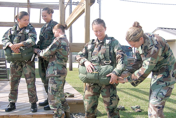 Senior Airman Lincy Hurtado gets help putting on her reserve parachute from Capt. Tara McLaughlin and Senior Airman Ashley-Ann Cady, while Senior Airman Polly-Jan Bobseine receives help from Capt. Lisa Vice. All are members of the 820th Security Forces Group here and earned their parachute wings. (Photo by Senior Airman S.I. Fielder)