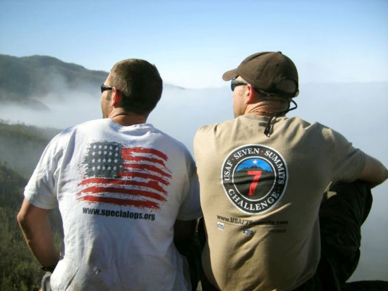 1st Lt. Mark Uberuaga (left) and Capt. Rob Marshall gaze upwards toward the summit of Mount Kilimanjaro during a break on Day 2 of their ascent. Lieutenant Uberuaga wears the Special Operations organization T-shirt, and Captain Marshall wears the T-shirt he designed for the Seven Summits Challenge. The men gave T-shirts to their climbing guides. (Courtesy photo/Capt. Nichelle Brokering)