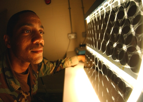 Staff Sgt. Corey Fletcher, 100th Maintenance Squadron Fabrications Flight, non-destructive inspection specialist, looks over an X-ray film of an MH-53 Pave Low helicopter engine air particle separator June 20. NDI specialists detect structural flaws, cracks, defects and foreign object damage in aircraft parts by using X-rays and fluorescent green penetrant. The cracks are usually invisible to the naked eye, but the NDI team finds them and make sure affected parts are taken out of service immediately. (U.S. Air Force photo by Staff Sgt. Tyrona Pearsall)