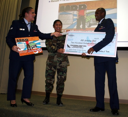 Airmen Against Drunk Driving Treasurer (left) Airman 1st Class Megan Stanton, 16th Medical Support Squadron, and AADD President Master Sgt. Myra Casanova, 16th Mission Support Squadron, hand Airman Basic Jeremy Bell, 505th Training Squadron, a check for $200 for his award-winning AADD poster. (U.S. Air Force Photograph by Jamie Haig)
