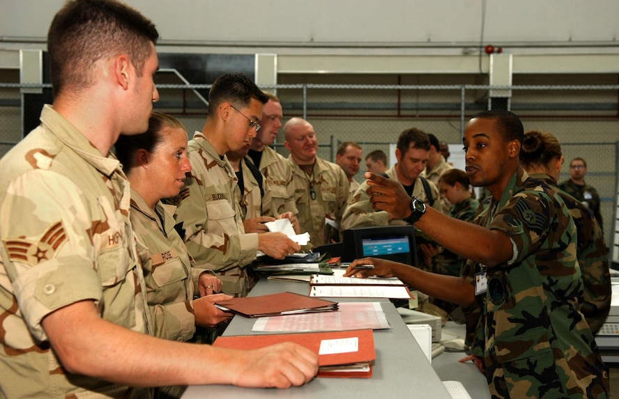 Staff Sgt. Donald Riley, 352nd Special Operations Squadron, right, verifies information in a mobility folder of another member of the 352nd SOG July 11. Military personnel flight representatives check folders to ensure identification cards, emergency records, dog tags and Air Force Form 245s are updated. The MPF has stations set up on the processing line to update administrative changes and dog tags. In a real world situation, a representative is on hand to escort deployable personnel back to MPF and update identification cards.  (U.S. Air Force photo by Staff Sgt. Tyrona Pearsall)