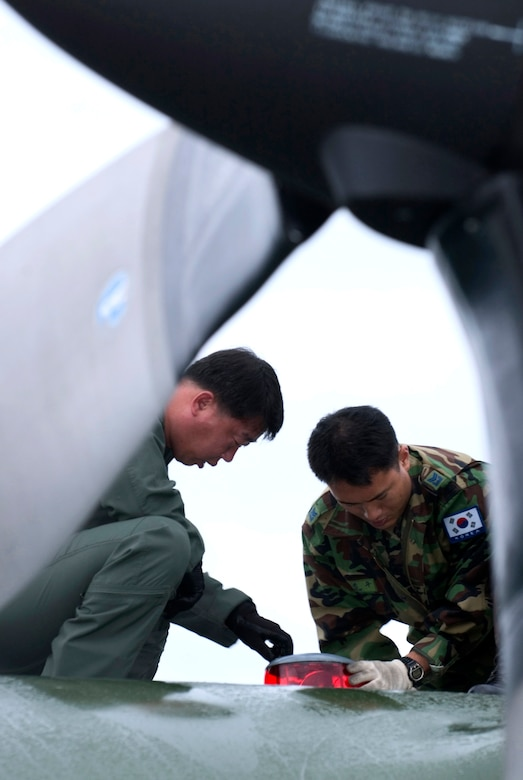 Chief Master Sgt. Jongkyu Lee and Master Sgt. Jinkoo Kim repair an anti-collision lamp on a C-130 Hercules at Elmendorf Air Force Base, Alaska, on July 25. They are members of the Korean air force and are participating in Cooperative Cope Thunder, a Pacific Air Forces exercise that ends Aug. 5. (U.S. Air Force photo/Senior Airman Garrett Hothan)