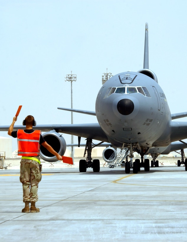 Airman 1st Class Nicholas Shoenhair marshals a KC-10 Extender to its parking spot at a deployed location in Southwest Asia. He is a KC-10 crew chief with the 380th Expeditionary Aircraft Maintenance Squadron. (U.S. Air Force photo/Staff Sgt. Jason Webb)