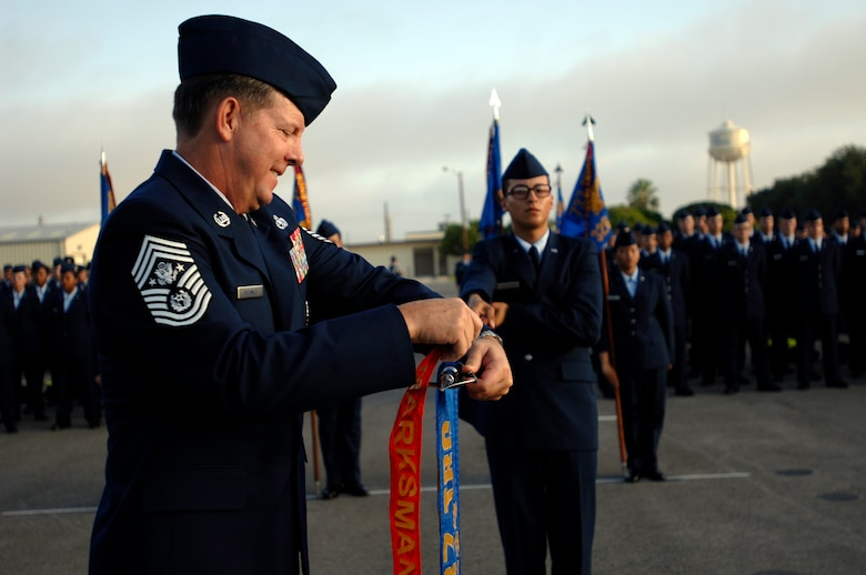"Chief Master Sgt. of the Air Force Rodney J. McKinley hangs the Marksman pennant on a flight's guidon signifying ""top flight"" during the Airman's coin ceremony at Lackland Air Force Base, Texas, on Aug. 7. The ceremony marks the transition of a trainee to an Airman.  Chief McKinley was a speaker during the ceremony. (U.S. Air Force photo/Tech. Sgt. Cecilio M. Ricardo Jr.)"