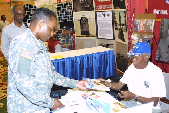 Retired Lt. Col. Alexander Jefferson hands an autographed copy of his book to Lt. Col. Gerald Torrence, Army War College, at the 35th Annual Tuskegee Airmen National Convention.