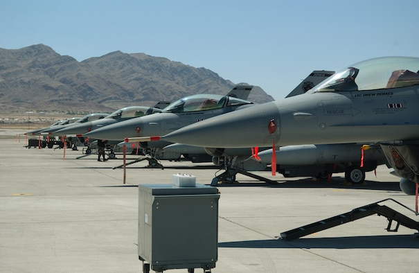 F-16 Fighting Falcons from the Air National Guard's 132nd Fighter Wing , Des Moines, Iowa, sit on the Nellis Air Force Base, Nev., flightline waiting for the night Red Flag launch on Aug. 8. Aircrews and maintainers from all U.S. services and several allied nations are taking part in Red Flag exercises, which prepare crews for  war in a highly realistic combat environment. (U. S. Air Force photo/Senior Airman Dan St. Pierre)