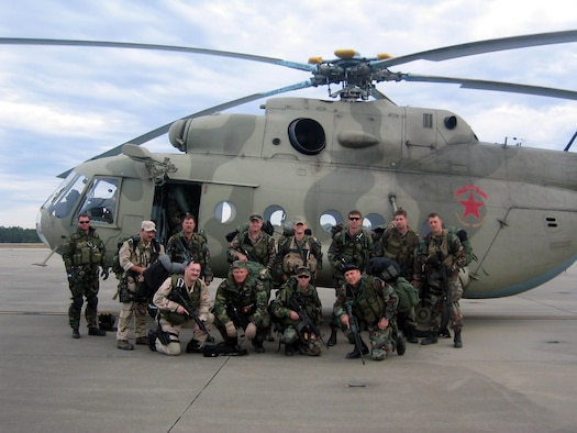Members of a 6th Special Operations Squadron Operational Aviation Detachment pose in front of an Mi-8 helicopter in a deployed location.  (Courtesy photographs)