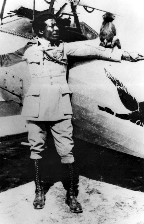 "Eugene Bullard with his pet monkey ""Jimmy"" beside a Nieuport 24 fighter of the 93rd Squadron (Escadrille) in August or September 1917. He flew with Jimmy tucked inside his coat on every combat mission. (U.S. Air Force photo)"