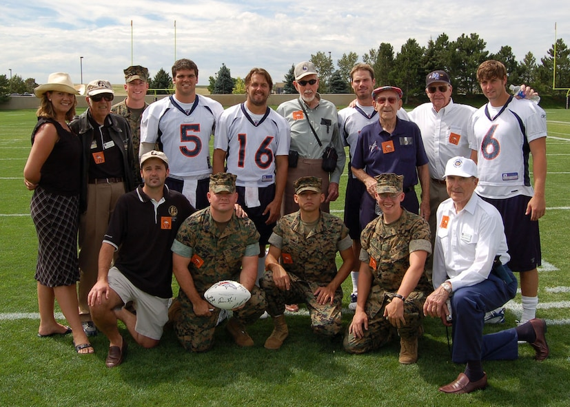 Marines from the Marine Cryptologic Support Battalion at Buckley Air Force Base in Colorado pose for a photo with representatives from the Greatest Generations Foundation, World War II veterans and quarterbacks from the Denver Broncos Aug. 9 at a Denver Broncos training camp practice. Pictured are: back row, left to right are: Elizabeth Crony, Lucky McGinty, Sgt. Brian Geraghty, Preston Parsons, Jake Plummer, Ray Heap, Bradlee Van Pelt, Leonard McKinney, E.E. Mischler, and Jay Cutler. Kneeling, left to right: Timothy Davis, Staff Sgt. Richard Molnar, Sgt. Manuel Perez, Lance Cpl. Christopher Pickens, and Rigney Sackley. The Marines were invited to the practice by the Greatest Generations Foundation to meet with World War II Veterans. The Greatest Generations Foundation is a non-profit educational organization that raises money to fully fund trips for veterans to revisit the sites of their former battlefields. (Photo by Air Force Staff Sgt. Aaron Cram)