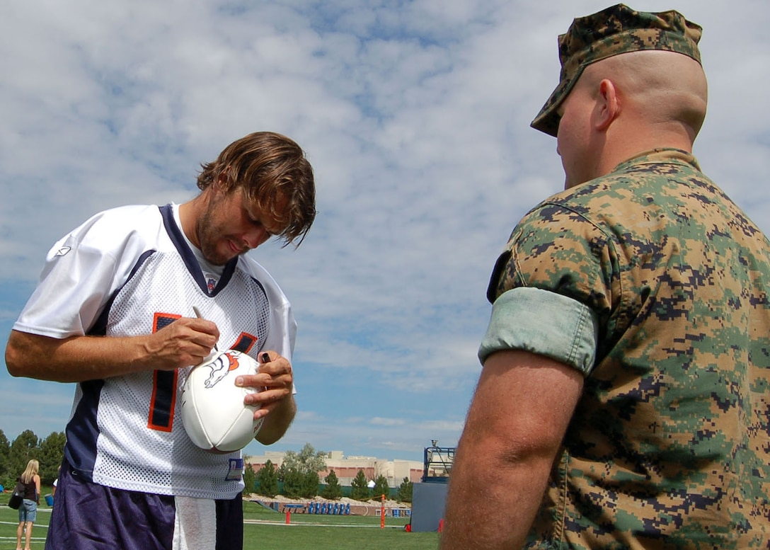 Denver Broncos starting quarterback Jake Plummer signs a football for Staff Sgt. Richard Molnar Aug. 9 at a Denver Broncos training camp practice. Molnar and three other Marines were invited to the practice by the Greatest Generations Foundation to meet with World War II Veterans. Molnar is assigned to the Marine Cryptologic Support Battalion at Buckley Air Force Base in Colorado. The Greatest Generations Foundation is a non-profit educational organization that raises money to fully fund trips for veterans to revisit the sites of their former battlefields. (Photo by Air Force Staff Sgt. Aaron Cram)