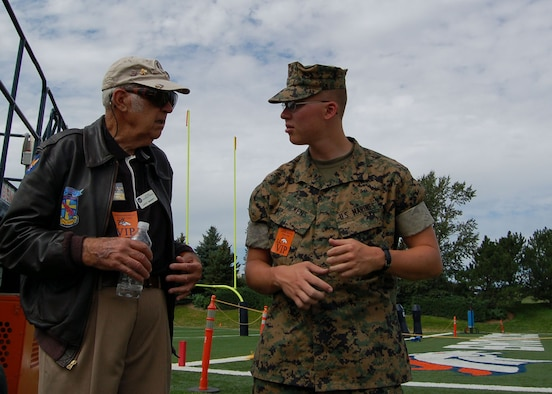 Lance Cpl. Christopher Pickens (right) talks with World War II veteran Lucky McGinty Aug. 9 at a Denver Broncos training camp practice. McGinty flew 29 combat missions into Germany as a B-17 gunner with the 95th Bomb Group. Pickens and thre other Marines were invited to the practice by the Greatest Generations Foundation to meet with World War II Veterans. Pickens is assigned to the Marine Cryptologic Support Battalion at Buckley Air Force Base in Colorado. The Greatest Generations Foundation is a non-profit educational organization that raises money to fully fund trips for veterans to revisit the sites of their former battlefields. (Photo by Air Force Staff Sgt. Aaron Cram)
