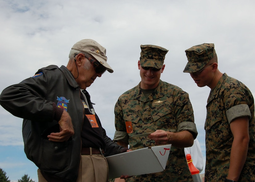 Sgt. Brian Geraghty (center) and Lance Cpl. Christopher Pickens (right) look at World War II veteran Lucky McGinty?s ID card from the 1940s Aug. 9 at a Denver Broncos training camp practice. McGinty flew 29 combat missions into Germany as a B-17 gunner with the 95th Bomb Group. The Marines were invited to the practice by the Greatest Generations Foundation to meet with World War II Veterans. The Marines are assigned to the Marine Cryptologic Support Battalion at Buckley Air Force Base in Colorado. The Greatest Generations Foundation is a non-profit educational organization that raises money to fully fund trips for veterans to revisit the sites of their former battlefields. (Photo by Air Force Staff Sgt. Aaron Cram)