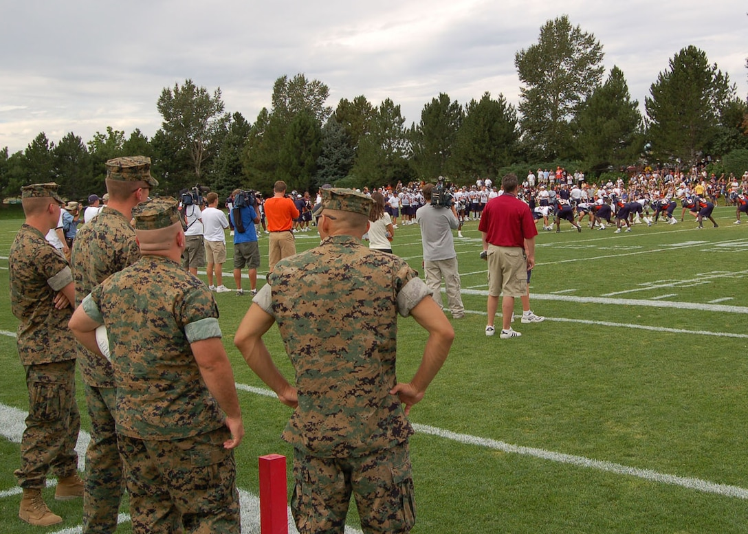 From left to right, Lance Cpl. Christopher Pickens, Sgt. Brian Geraghty, Staff Sgt. Richard Molnar, and Sgt. Manuel Perez watch a Denver Broncos training camp practice Aug. 9 at the Denver Broncos Football Club. The Marines were invited to the practice by the Greatest Generations Foundation to meet with five World War II veterans. The Marines are assigned to the Marine Cryptologic Support Battalion at Buckley Air Force Base in Colorado. The Greatest Generations Foundation is a non-profit educational organization that raises money to fully fund trips for veterans to revisit the sites of their former battlefields. (Photo by Air Force Staff Sgt. Aaron Cram)