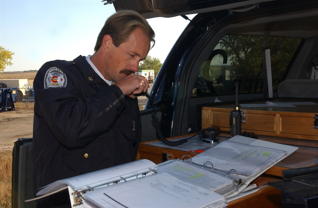 BUCKLEY AIR FORCE BASE, Colo. -- Steve Zigan, lead firefighter with the 460th Civil Engineer Squadron, updates the unit control center on the findings at the scene of a simulated F-16 Fighting Falcon mishap during a full spectrum threat response exercise Oct. 6, 2005 at Buckley Air Force Base, Colo. (U.S. Air Force photo by Airman 1st Class Logan Tuttle)