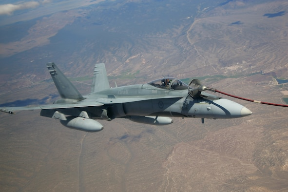 A CF-18M from the 409th Tactical Fighter Squadron, Cold Lake, Canada, takes on fuel Aug. 15 from a CC-130T tanker, 17th Wing, 435th Squadron, Winnipeg, Canada. Canadian air forces are taking part in the first two-week period of exercise Red Flag, which ends 18 Aug. The CF-18s are performing air-to-ground strike operations during Red Flag, which pits friendly forces against Air Force Aggressor F-15s and F-16s over the 12,000-square-mile Nevada Test and Training Range Complex. (Photo courtesy Paul Ridgway, Typhire Photography)