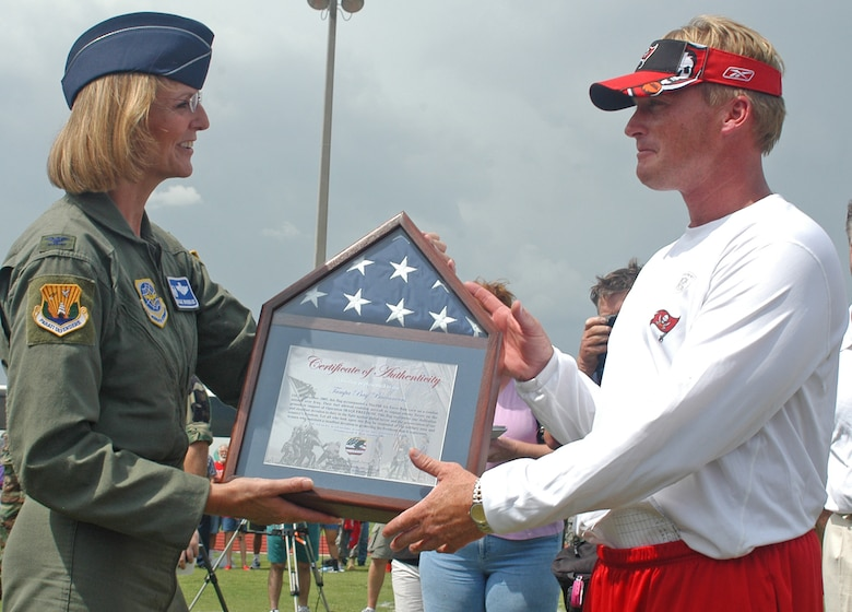 Col. Maggie Woodward, 6th Air Mobility Wing commander, presents a framed flag to