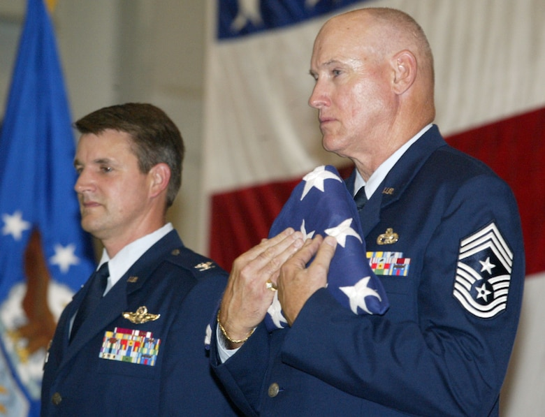 94th Airlift Wing Command Chief James Michael West holds the retirement flag given to him during his retirement ceremony on the August unit training assembly.  To his right, Col. Heath Nuckolls, 94th Airlift Wing commander, officiated the ceremony.