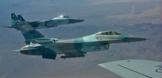 "F-16 and F-15 Aggressor aircraft from Nellis AFB, Nev., fly in formation with a KC-135 tanker from the 6th Air Mobility Wing, MacDill AFB, Fla., Aug. 18. The Aggressors act as ""enemy"" aircraft during the Red Flag exercise which continues through Sept. 2. The F-15 Aggressors belong to the 65th Aggressor Squadron, while the F-16s belong to the 64th Aggressor Squadron. (U.S. Air Force photo/Mike Estrada)"