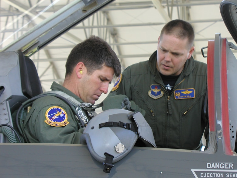 """Lt. Col. Nathan Hill, 25 Flying Training Squadron commander, prepares his """"honorary commander,"""" Mr. Brian Henson of Henson Construction, to take a flight in a T-38C Talon aircraft. Part of the squadron commander's responsibility is maintaining and facilitating off-base community relations contacts. One way to do that is to have an honorary commander and orientate him or her to the mission of the unit, the wing and the Air Force. (U.S. Air Force photo by Capt. Tony Wickman)"""