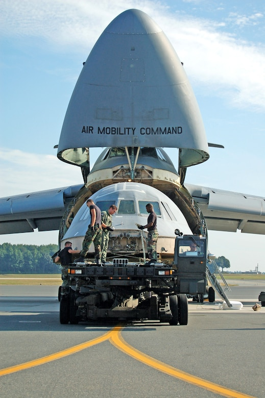 (Left to right) Staff Sgt. John Rollins, Airman 1st Class Shain Brower, Staff Sgt. Stuard Smith II and Senior Airman Joseph Moseley load a C-5 Galaxy flight deck onto another C-5 for transport to Robins Air Force Base, Ga. The flight deck from the C-5 that crashed April 3 will be used to as a training simulator. Sergeant Rollins and Airmen Brower and Moseley are assigned to the 436th Aerial Port Squadron; Sergeant Smith is with the 9th Airlift Squadron. (U.S. Air Force photo/Airman 1st Class James Bolinger)