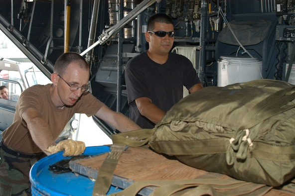 Left, Staff Sgts. Sean Herzog and Joel Salazar, 317th OSS, push in a pallet of cargo onto a C-130. The tanks contain water to simulate the weight that would be dropped.