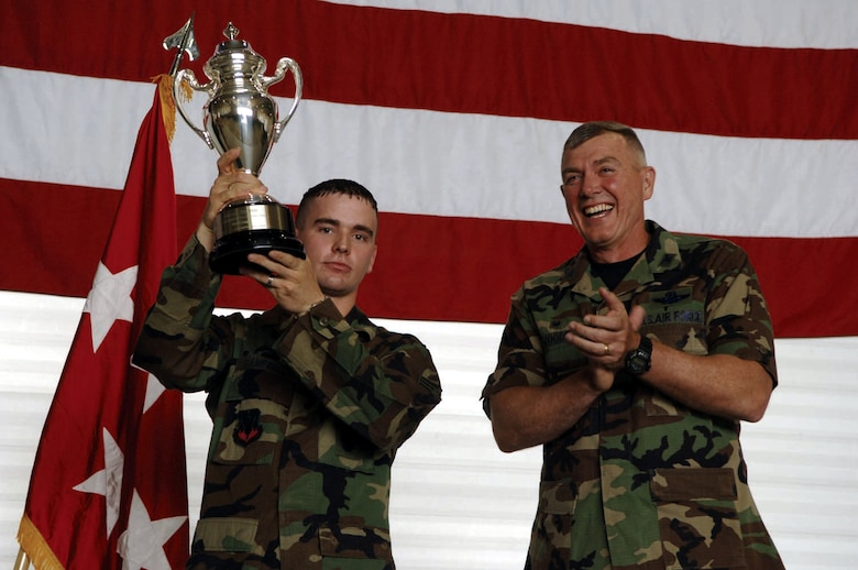 MINOT AIR FORCE BASE, N.D. -- Senior Airman Neil Campbell, 5th Security Forces Squadron, holds up the Omaha trophy with Col. Eldon Woodie, 5th Bomb Wing commander. The 5th Bomb Wing won the trophy for its strategic aircraft operations in 2005. (U.S. Air Force photo by Airman 1st Class Christopher Boitz)