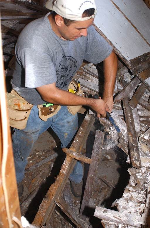 Master Sgt. Dean Ross pulls up rotted flooring in the hurricane-damaged Biloxi home of Alice Schuler, whose late husband, David, was an Air Force veteran. The project is part of continuing humanitarian relief operations in communities surrounding Keesler Air Force Base, Miss., since Hurricane Katrina. Sergeant Ross is with the 332nd Training Squadron. (U.S. Air Force photo/Kemberly Groue)