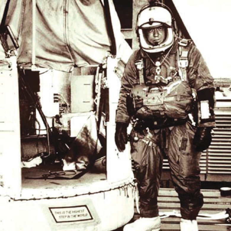 """Capt. Joseph Kittinger stands outside the balloon gondola Excelsior III. The sign on the gondola step reads """"This is the highest step in the world."""""""