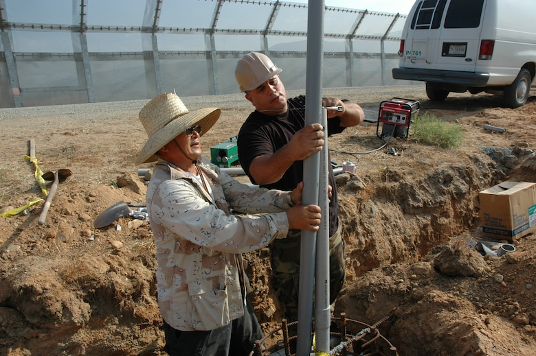 Staff Sgt. Ron Henderson, California Air National Guard civil engineer, cuts lighting poles with a civilian contractor while deployed to the San Diego Border. (U.S. Air Force photo by Lt. Col. Mark Moritz, 163 ARW)