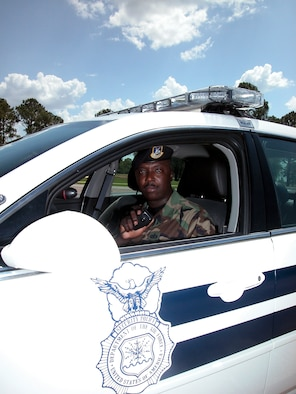 """908th Security Force's Squadron's Staff Sgt. Richard Peterson answers a call on his patrol car radio. A member of the Maxwell AFB, Ala.-based 908th Airlift Wing Air Force Reserve unit, Sergeant Peterson is a highly decorated civilian law enforcement officer who is one of the State of Alabama's top police investigators. The Air Force Reservist's role in assisting the Rochester, N.Y., Police Department solve several nearly 10-year-old schoolgirl rape cases was acknowledged in an Arts & Entertainment network's TV series """"Cold Case Files"""" segment that first aired in April 2006.  (U.S. Air Force Photo by Lt. Col. Jerry Lobb)"""