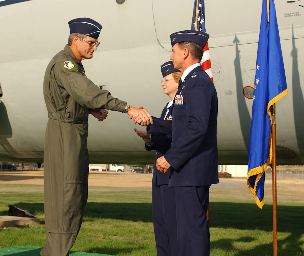 Brig. Gen. David Young, 59th Medical Wing commander, presents wing coins to Maj. Gen. Melissa Rank, assistant Air Force surgeon general for medical force development and nursing services, and Col. (Dr.) Byron Hepburn, command surgeon for Headquarters Air Mobility Command, during the C-9 dedication ceremony at Lackland Air Force Base, Texas, Aug. 31. (U.S. Air Force photo/Master Sgt. Kimberly Yearyean-Siers)