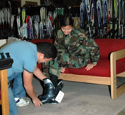 James Asher, recreation assistant at Outdoor Recreation, helps Airman 1st Class Juliana Nualta, 341st Comptroller Squadron, get measured for snowboarding equipment.